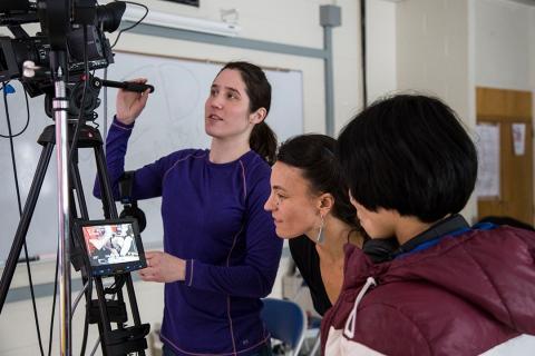 Three women operate a film camera.